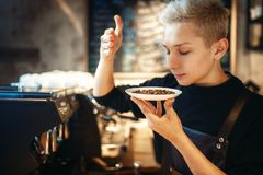 Young male barista sniffs fresh coffee beans. Cafe counter on background. Professional espresso preparation by barman in cafeteria, bartender occupation Royalty Free Stock Images
