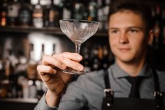 Young male barman holding a clear cocktail glass. On the blurred background of bar counter Stock Photos