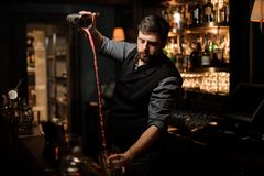 Bartender mixing the alcohol cocktail in shaker. Young male bartender with beard mixing the alcohol cocktail in steel shaker stock image