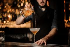Male bartender makes alcohol cocktail using glass with strainer stock photos