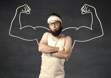 Young weak man with drawn muscles. A young male with beard and glasses posing in front of grey background, thinking about lifting weight with big muscles Royalty Free Stock Photos