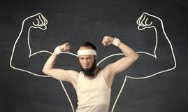 Young weak man with drawn muscles. A young male with beard and glasses posing in front of grey background, thinking about lifting weight with big muscles Stock Photos