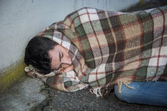 Young male beggar on city sidewalk sleeping Stock Images
