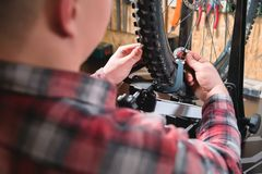 Young male bicycle repairman with a specialized wrench on a stand in the workshop, tightening the spokes of the wheel. Eliminating the beating of the rim royalty free stock photo