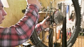 Young male bicycle repairman with a specialized wrench on a stand in the workshop, tightening the spokes of the wheel. Eliminating the beating of the rim stock footage