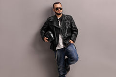 Young male biker leaning against a wall Stock Photos