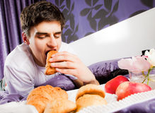 Young male biting croissant bed Royalty Free Stock Images