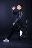 Young male black-haired pop singer singing to microphone Royalty Free Stock Photos