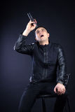 Young male black-haired pop singer sings to microphone Royalty Free Stock Images