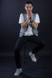 Young male black-haired singer posing singing to microphone Stock Photography