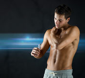 Young male bodybuilder applying pain relief gel Royalty Free Stock Image