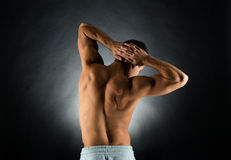 Young male bodybuilder from back. Sport, bodybuilding, strength and people concept - young man standing over black background from back Stock Photography