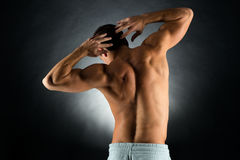 Young male bodybuilder from back. Sport, bodybuilding, strength and people concept - young man standing over black background from back Royalty Free Stock Photography