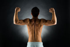 Young male bodybuilder from back. Sport, bodybuilding, strength and people concept - young man standing over black background from back and flexing muscles Stock Photo