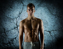 Young male bodybuilder with bare muscular torso. Sport, bodybuilding, strength and people concept - young man with bare muscular torso standing over concrete Stock Images