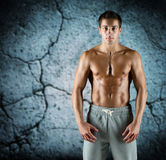 Young male bodybuilder with bare muscular torso. Sport, bodybuilding, strength and people concept - young man with bare muscular torso standing over concrete Stock Photo