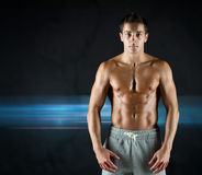 Young male bodybuilder with bare muscular torso. Sport, bodybuilding, strength and people concept - young man with bare muscular torso standing over dark Stock Images