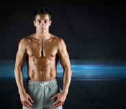 Young male bodybuilder with bare muscular torso. Sport, bodybuilding, strength and people concept - young man with bare muscular torso standing over dark Royalty Free Stock Photography