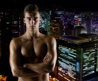 Young male bodybuilder with bare muscular torso. Sport, bodybuilding, strength and people concept - young man with bare muscular torso standing over night city Royalty Free Stock Photos