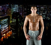 Young male bodybuilder with bare muscular torso. Sport, bodybuilding, strength and people concept - young man with bare muscular torso standing over night city Stock Photography