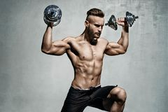 Young male bodybuilder doing exercise with heavy weight dumbbells Royalty Free Stock Image