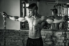 Young male bodybuilder in gym posing with metal chains Stock Photography