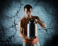 Young male bodybuilder holding jar with protein. Sport, bodybuilding, strength and people concept - young man standing holding jar with protein over concrete Stock Photography