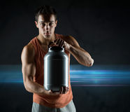 Young male bodybuilder holding jar with protein. Sport, bodybuilding, strength and people concept - young man standing holding jar with protein over dark Stock Photos