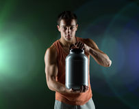 Young male bodybuilder holding jar with protein. Sport, bodybuilding, strength and people concept - young man standing holding jar with protein over dark Royalty Free Stock Images