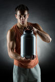 Young male bodybuilder holding jar with protein. Sport, bodybuilding, strength and people concept - young man standing holding jar with protein over gray Stock Images