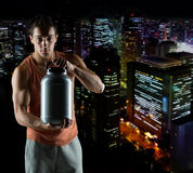 Young male bodybuilder holding jar with protein. Sport, bodybuilding, strength and people concept - young man standing holding jar with protein over night city Royalty Free Stock Photo