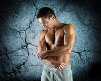 Young male bodybuilder injured touching elbow. Pain, sport, bodybuilding, health and people concept - young male bodybuilder touching injured elbow over concrete Royalty Free Stock Photos