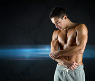 Young male bodybuilder injured touching elbow. Pain, sport, bodybuilding, health and people concept - young male bodybuilder touching injured elbow over dark Royalty Free Stock Photo