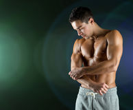 Young male bodybuilder injured touching elbow Royalty Free Stock Image