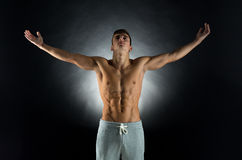 Young male bodybuilder with raised hands Stock Image