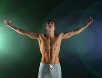 Young male bodybuilder with raised hands Royalty Free Stock Photos