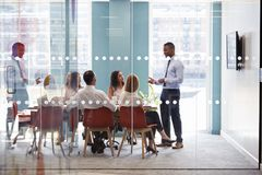 Young male boss stands addressing business team at meeting royalty free stock images