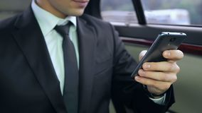 Young male boss using his smartphone while sitting in car, business meeting. Stock footage stock footage