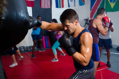 Young male boxer punching bag Stock Photography
