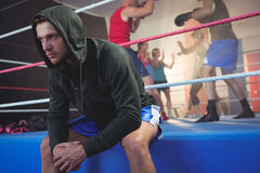 Young male boxer sitting on boxing ring at fitness studio Stock Image