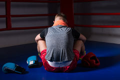 Young male boxer with a towel around his neck sitting backwards. Near lying boxing gloves and helmet in regular boxing ring in a gym Stock Photos