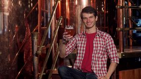 Young male brewer examining freshly brewed beer, working at his brewery royalty free stock photography