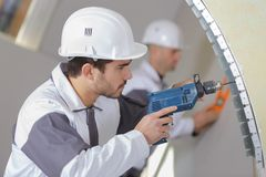 Young male builder drilling wall with drill perforator Royalty Free Stock Photo