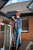 Young male builder standing on stepladder and repairing rooftop. Male builder standing on stepladder and repairing rooftop Stock Images