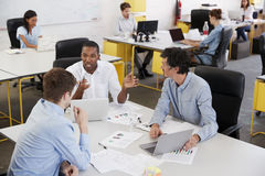 Young male business team brainstorming in busy office Royalty Free Stock Images