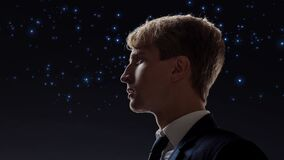 Young male businessman on the background of the starry sky.