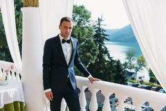 Young male businessman in a classic black suit with a white shirt and a bow tie. Portrait of the groom waiting for the. Bride on a wedding day standing on a Stock Photo