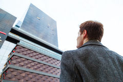 Young male businessman is dreaming. View from the back of man from the bottom up to high-rise office building Stock Image
