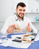 Young male businessman earning money easily online in Internet. Young cheerful positive male businessman earning money easily online in Internet Royalty Free Stock Photo