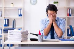 The young male businessman employee unhappy with excessive work. Young male businessman employee unhappy with excessive work royalty free stock images